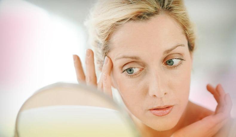 Kobieta pokazuje starzenie się skóry